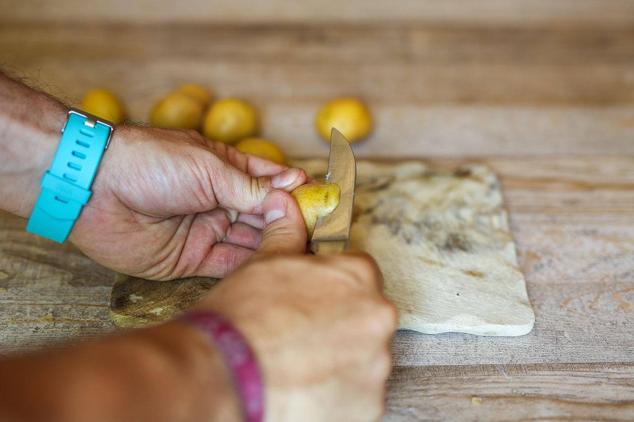 Entferne mit einem Messer die Schale von den Kartoffeln