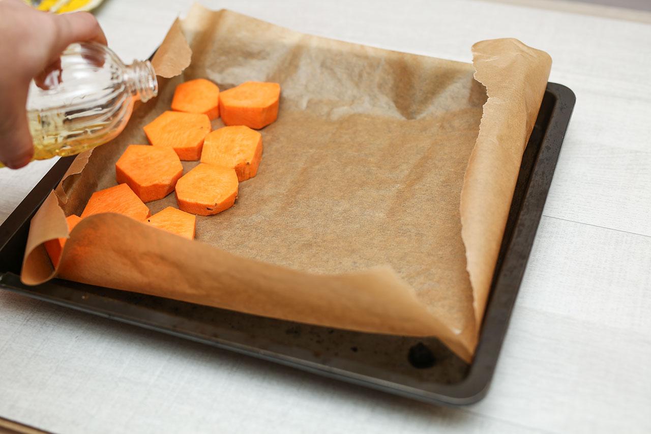 Heiße den Ofen auf 180 Grad vor. Lege das Backblech mit Backpapier aus. Dann legst du die Süßkartoffelscheiben auf das Backblech und gießt etwas Rapsöl darüber. Schiebe das Backblech in den Ofen und lasse die Süßkartoffeln ca. 20 Minuten backen.