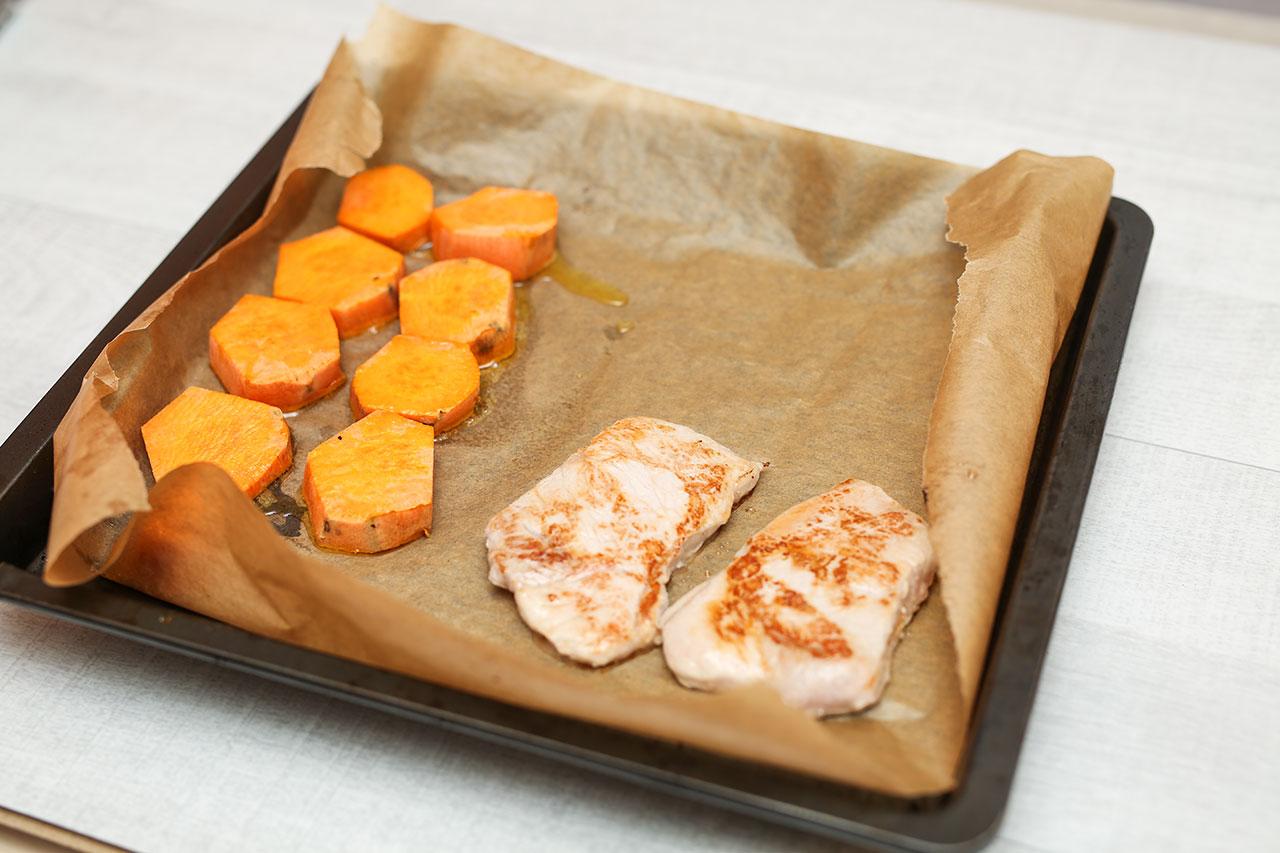 Lege die Hähnchenbrustfilet auf das Backblech und lass die Süßkartoffeln und das Fleisch ca. 10 Minuten im Ofen garen.