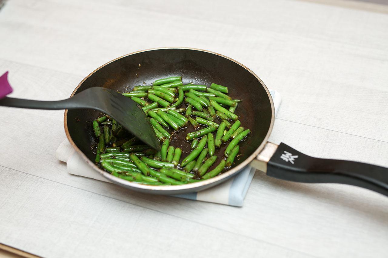 Wasche die Bohnen und schneide die Enden ab. Knoblauch abziehen. Brate in der beschichteten Pfanne die Bohnen und den Knoblach mit etwas Butter an. Dann gibst du Thymian und den Honig dazu.