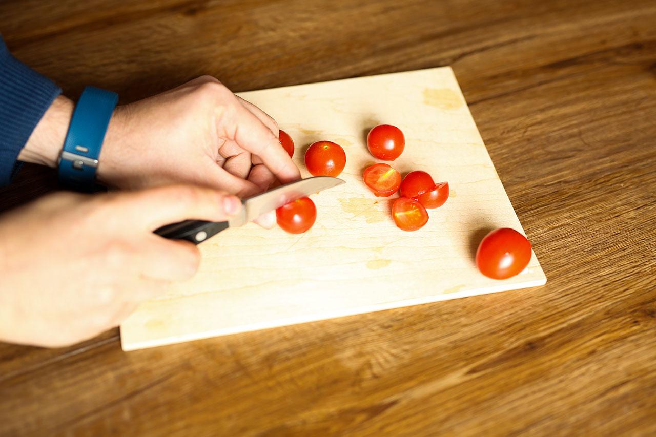 Tomaten waschen und halbieren. Knoblauch schälen und in kleine Würfel schneiden