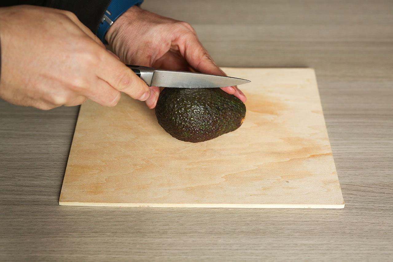 Für den Dip halbierst du die Avocado und nimmst den Kern heraus. Dann schälst du die Avocado.