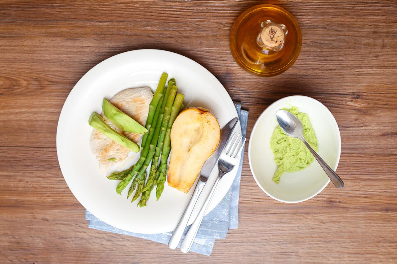 Zum Schluss garnierst du den grünen Spargel mit dem Hähnchenbrustfilet sowie der Birne und deinen Avocadoscheiben und dem Dip.