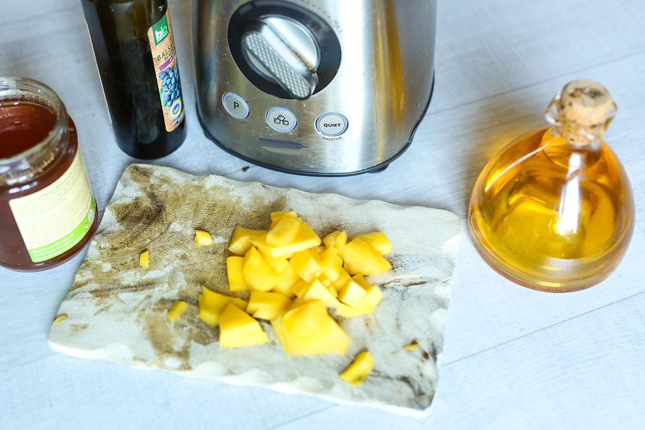 Mixe für das Dressing die Hälfte der Mango mit einem Löffel Honig und einem Löffel Balsamico sowie Olivenöl
