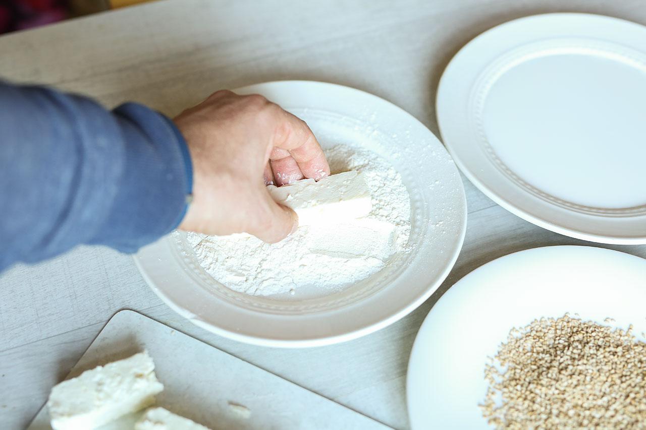 In dem ersten Teller füllst du Mehl, in den zweiten Teller Milch und in den dritten Teller Sesamkörner. Dann wendest du das Fetastück zuerst im Mehl, dann in Milch und zum Schluss in den Sesamkörnern