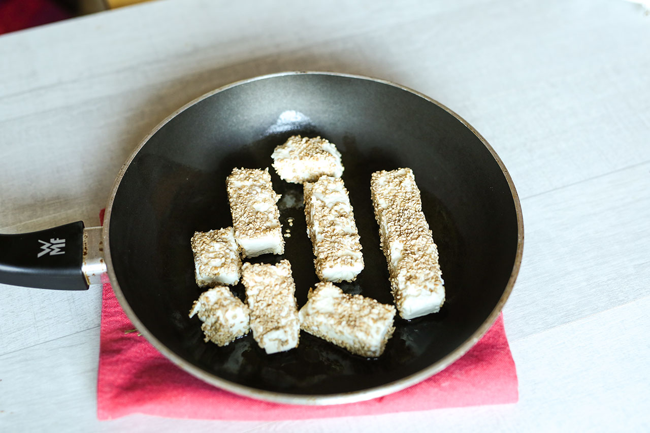Erhitze Rapsöl in einer beschichteten Pfanne und brate die Fetakäsestücke von allen Seiten ca. 3-4 Minuten bis sie eine leichte bräunliche Farbe haben