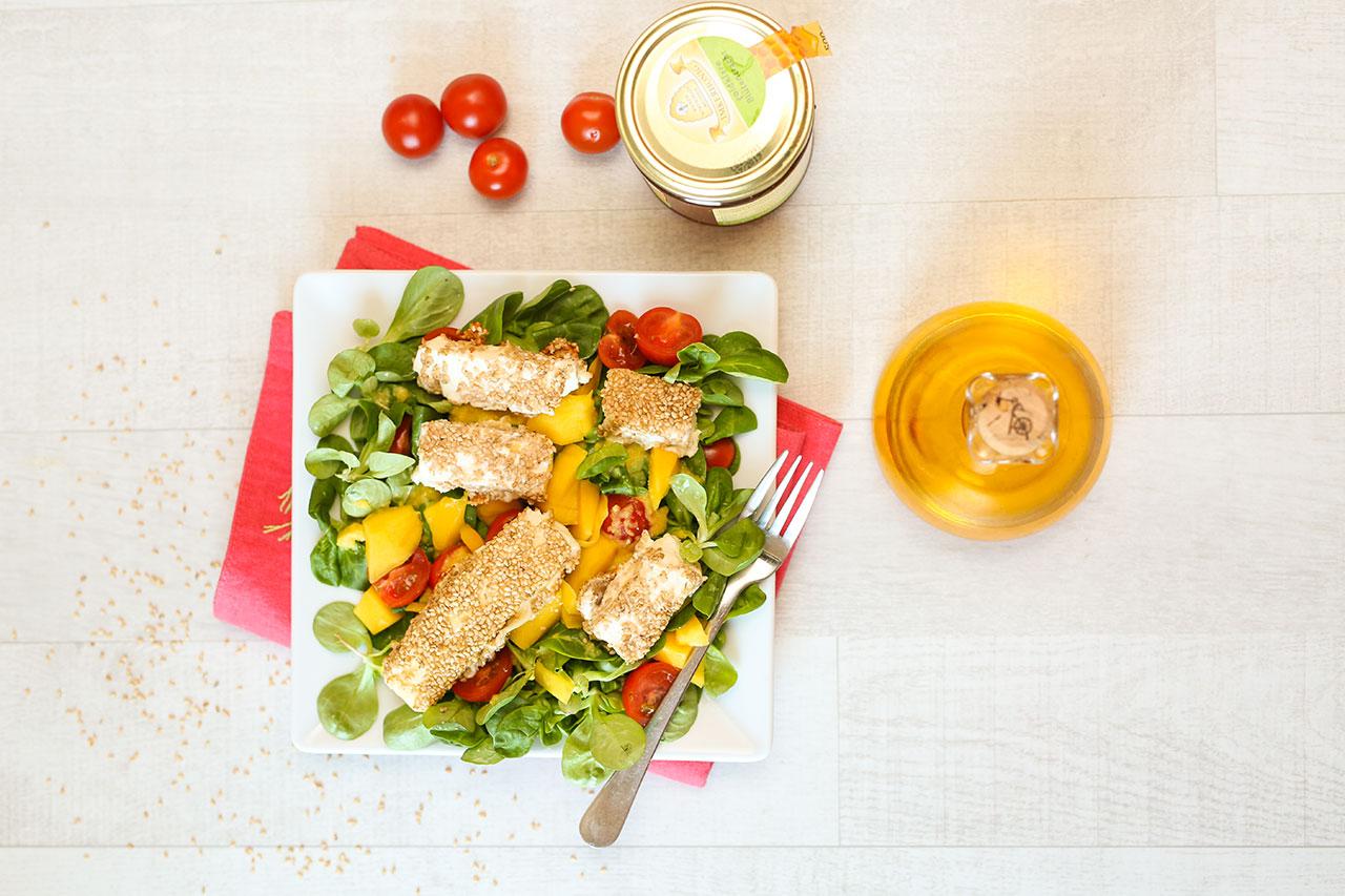 Auf einem Teller richtest du den Blattsalat mit dem Dressing, Mango- und Tomatenstücke sowie den Fetabratlingen lecker an