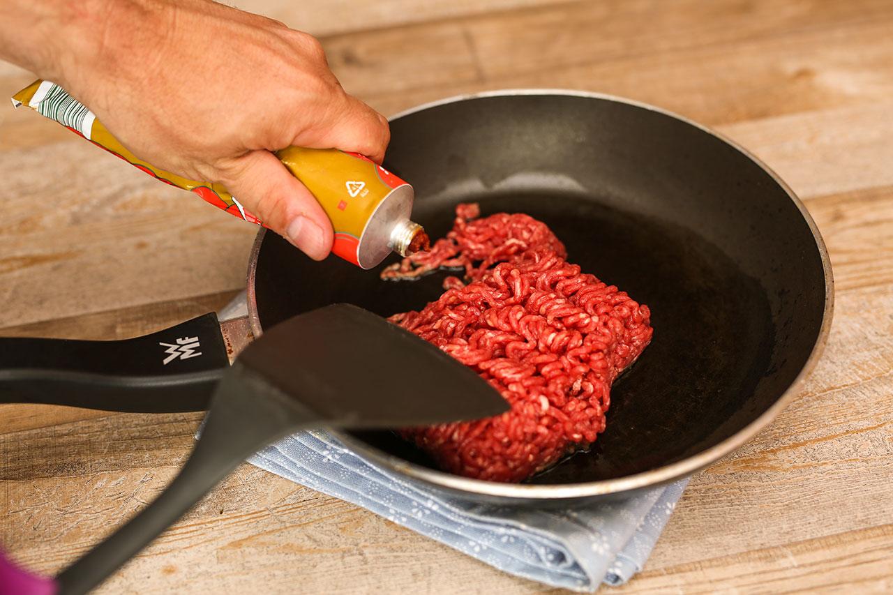 Brate das Hackfleisch mit etwas Rapsöl an und füge Tomatenmark hinzu