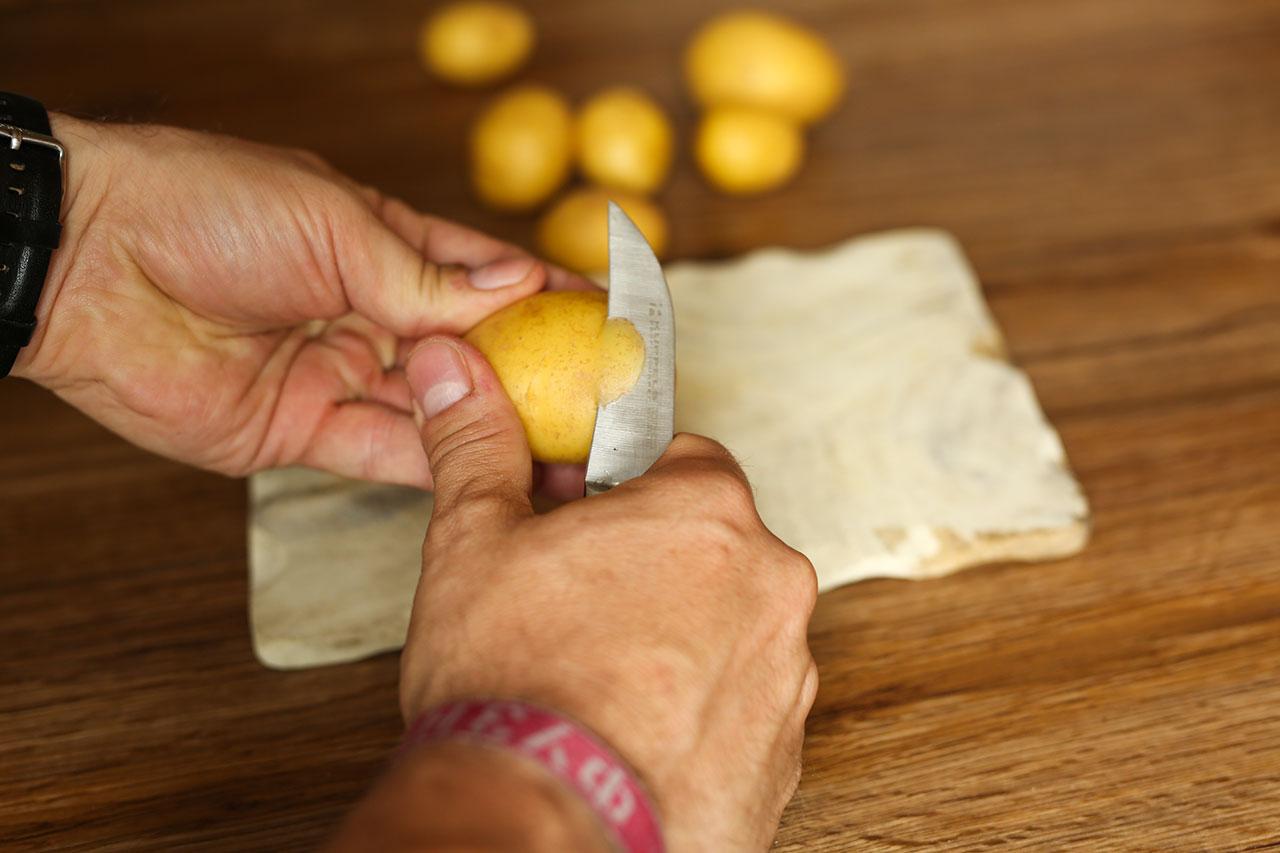 Backofen auf 150 Grad vorheizen und Kartoffeln schälen und achteln