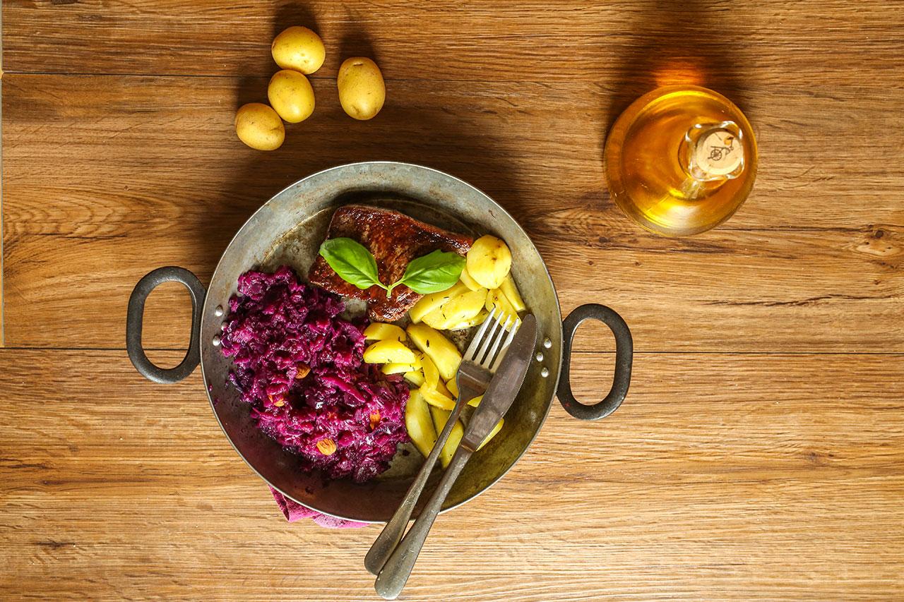 Das Rinderfilet legst du nach dem Anbraten in den Ofen zu den Kartoffeln und lässt es dort ca. 8-10 Minuten. Dann alles auf einem Teller lecker anrichten. Füge noch unter den Rotkohl ein paar Mandeln hinzu.