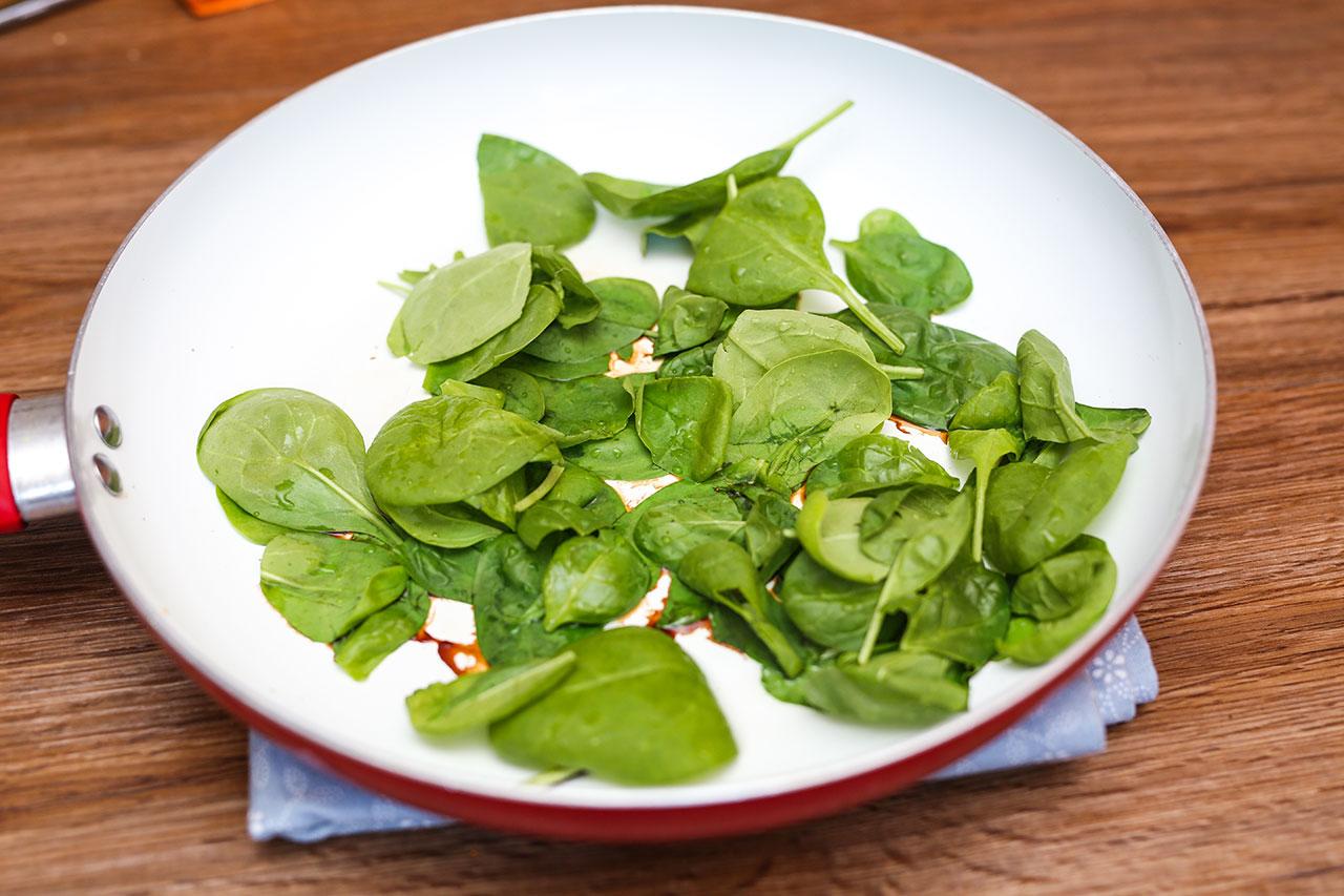 Erhitze in einer weiteren beschichteten Pfanne etwas Öl und gebe 2 EL Wasser hinzu. Dann fügst du den Blattspinat hinzu und dazu etwas Sojasoße. Dünste den Spinat 2-3 Minuten bis er zusammengefallen ist.