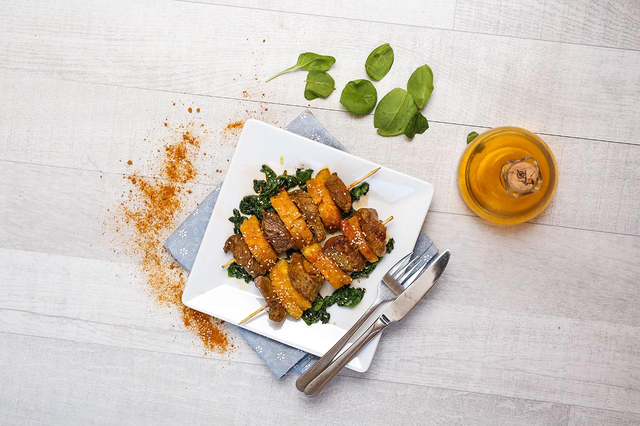 Garniere den Spieß auf einem Teller mit dem Blattspinat und streue die Sesamkörner darauf.