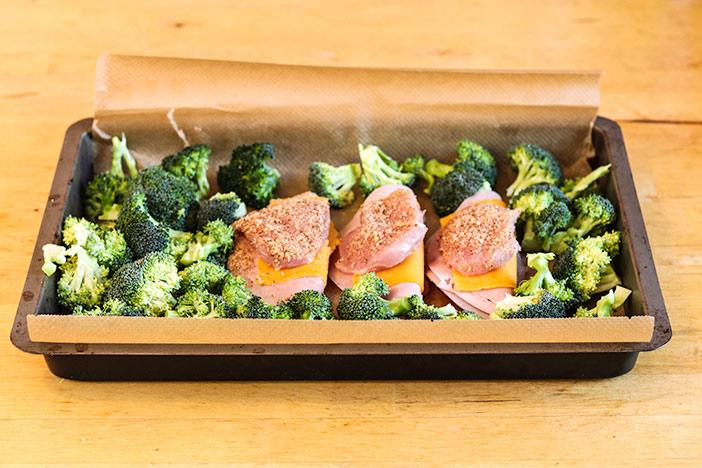 Cordon Bleu und Brokkoli auf dem Backblech verteilen