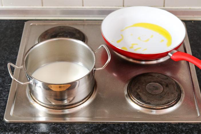 Milch im Topf und Öl in der Pfanne erwärmen